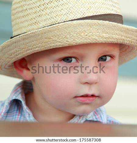 Portrait of a beautiful little boy in a summer hat outdoors - stock photo