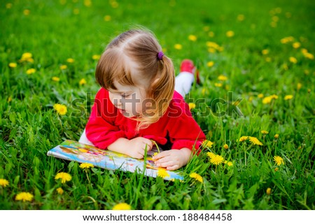 portrait of a beautiful little girl. baby lying on the grass and reading a book - stock photo