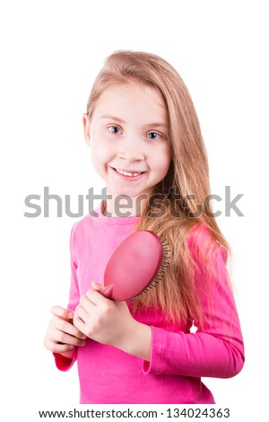 Portrait of a beautiful little girl brushing her long  hair isolated on white. Hair care concept.
