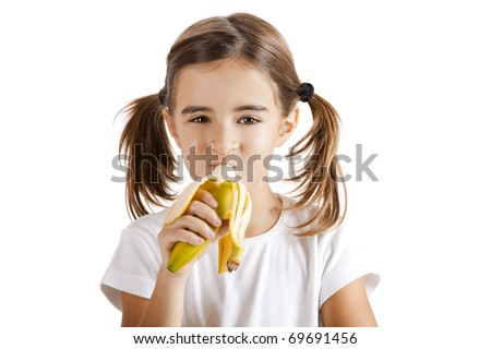 Portrait of a beautiful little girl eating a banana - stock photo
