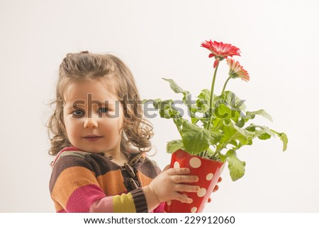Portrait of a beautiful little girl holding vase with flowers looking at the camera smileing on white background - stock photo