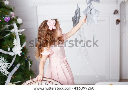 Portrait of a beautiful little girl in a pink dress in the interior with Christmas decorations. Baby girl grabs and catches toy star - an element of a Christmas decor - stock photo