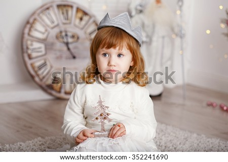 Portrait of a beautiful little girl in a white dress and a crown in the interior with Christmas decorations. Little Princess
