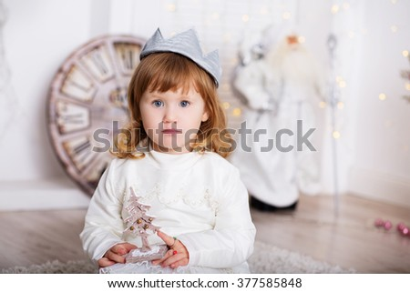 Portrait of a beautiful little girl in a white dress and a crown in the interior with Christmas decorations. Little Princess With a wooden toy Christmas tree - stock photo