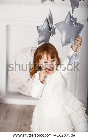 Portrait of a beautiful little girl in a white dress in the interior with Christmas decorations. Baby girl grabs and catches toy star - an element of a Christmas decor - stock photo