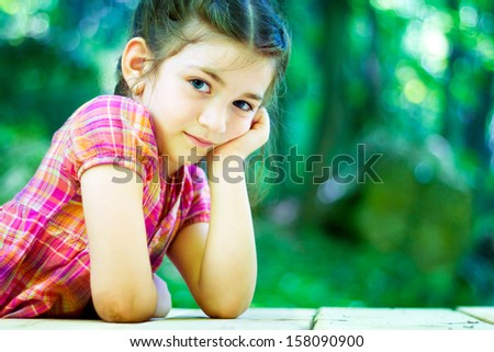 Portrait of a beautiful little girl in the forest  - stock photo