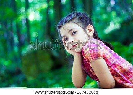 Portrait of a beautiful little girl in the forest. With hands on chin - stock photo
