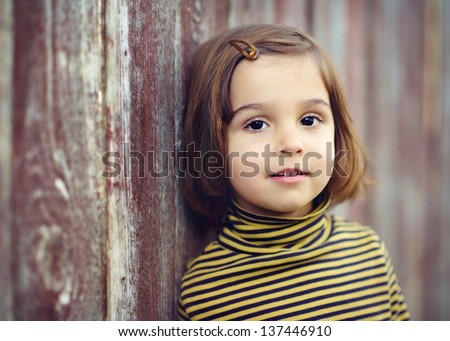 Portrait of a beautiful little girl leaning on a fence - stock photo