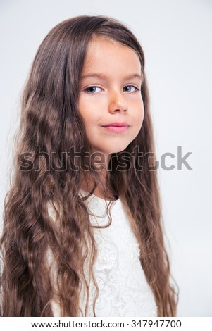 Portrait of a beautiful little girl looking at camera isolated on a white background - stock photo