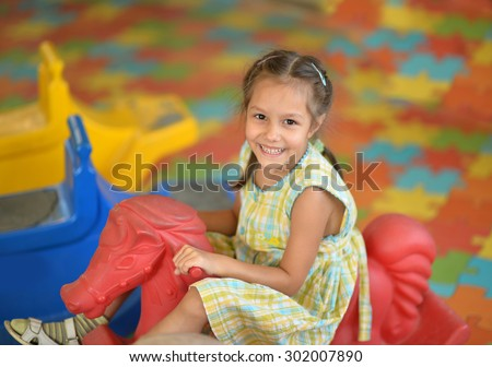 Portrait of a beautiful little girl on  rocking horse. - stock photo