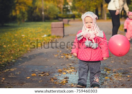 portrait of a beautiful little girl who is walking in an autumn park with a red balloon. The concept of family photo, love, mutual understanding, love of children
