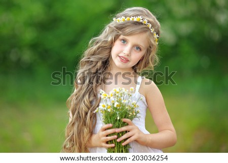 portrait of a beautiful little girl with chamomile - stock photo