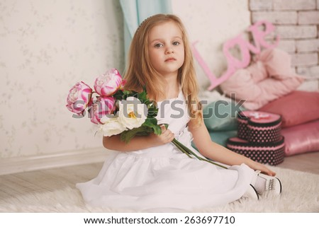 Portrait of a beautiful little girl with flowers - stock photo