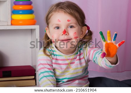 Portrait of a beautiful little girl with her  hand in paint, ready to prints - stock photo