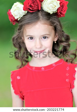 portrait of a beautiful little girl with rose wreath