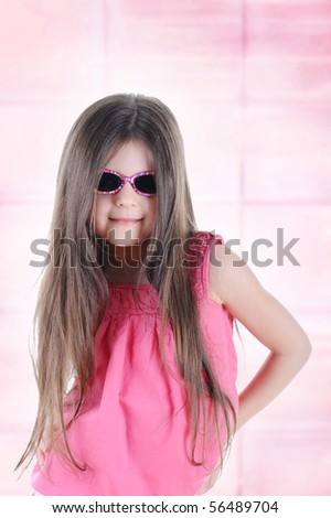 Portrait of a beautiful little long-haired brunette in sunglasses. - stock photo