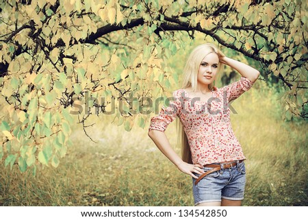 Portrait of a beautiful long-haired blonde girl in the autumn park. Perfect hair and make-up. Retro (80s) style. Outdoor shot - stock photo