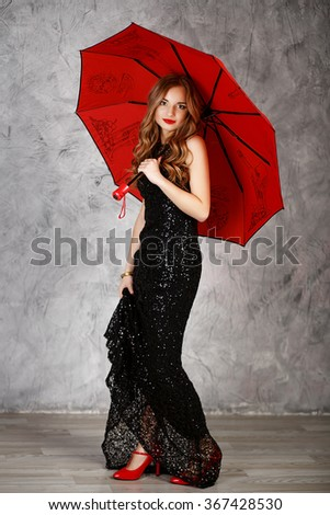 Portrait of a beautiful long-haired young girl in black evening dress with a red umbrella. Young woman with red umbrella - stock photo
