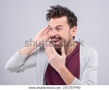 Portrait of a beautiful man secretly eavesdropping on a private conversation and laughs. The human face, expression, emotion, body language. - stock photo
