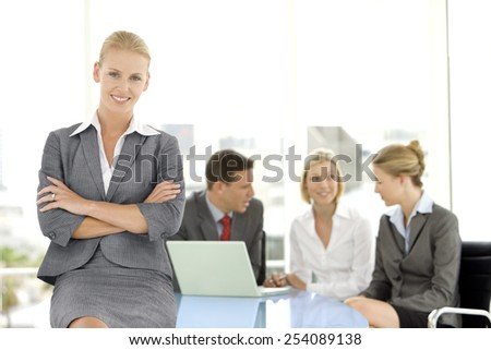 Portrait of a beautiful manager with business team in the background - stock photo