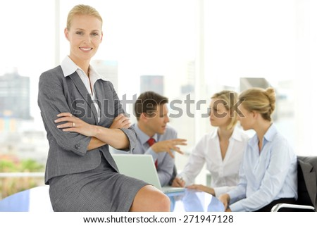 Portrait of a beautiful manager with business team working together in the background. - stock photo
