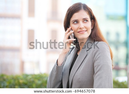 Portrait of a beautiful mature business woman in smart phone conversation in financial city exterior, smiling. Professional female wearing smart clothes in sunny outdoors, using technology.