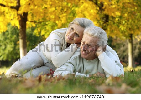 portrait of a beautiful mature couple lying on the autumn leaves - stock photo