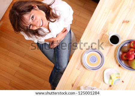 Portrait of a beautiful mature woman sitting in the kitchen. Focus on the Face. - stock photo