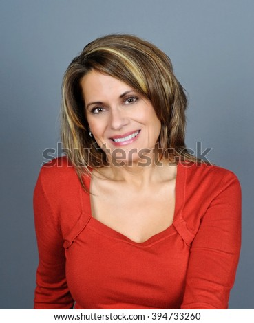 Portrait of a Beautiful Mature Woman wearing a Red Sweater   - stock photo