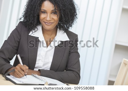 Portrait of a beautiful middle aged African American woman or businesswoman sitting relaxing, writing in a diary or personal organiser & smiling - stock photo