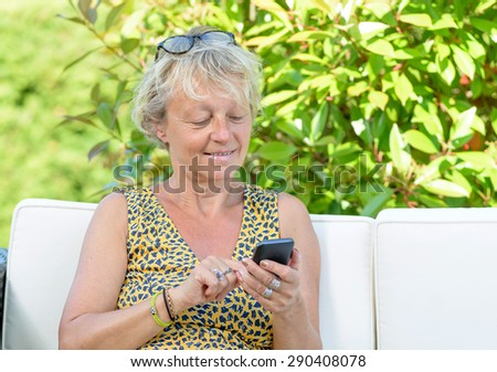 portrait of a beautiful middle-aged woman on phone on her sofa outside - stock photo