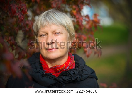Portrait of a beautiful middle-aged woman outdoors. Selective focus. - stock photo
