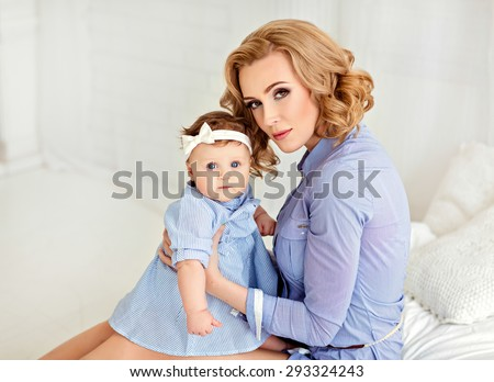 Portrait of a beautiful mom blonde and a little girl baby with blue eyes in blue striped dress sitting on a white bed.