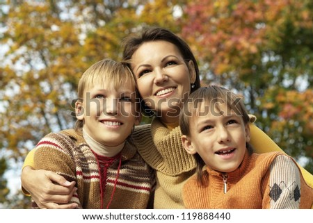 portrait of a beautiful mother and her children on autumn background