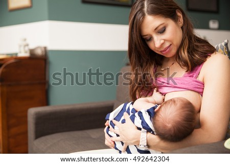 Portrait of a beautiful mother breastfeeding her newborn baby while sitting in a couch at home