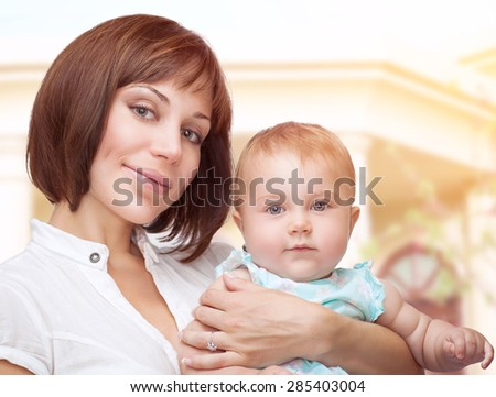 Portrait of a beautiful mother holding cute adorable baby, standing outdoor near their big new house, happy family life - stock photo