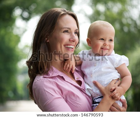 Portrait of a beautiful mother holding cute baby outdoors