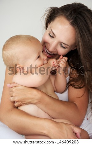Portrait of a beautiful mother hugging baby laughing together