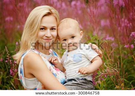 Portrait of a beautiful mother's blonde and adorable smiling baby boy on the background of grass fireweed in the summer, close-up - stock photo