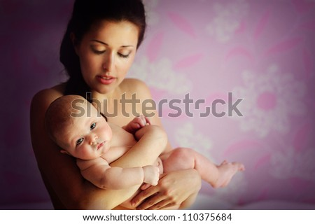 Portrait of a beautiful mother with her newborn baby indoor - stock photo