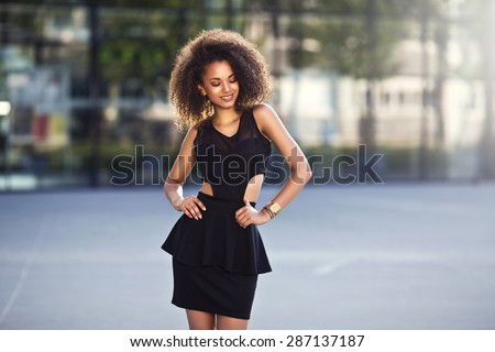 Portrait of a beautiful natural young African woman with afro smiling happiness. Outdoor portrait in sun