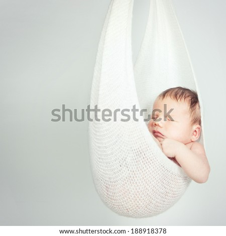 Portrait of a beautiful newborn baby sleeping in a hammock over gray background - stock photo