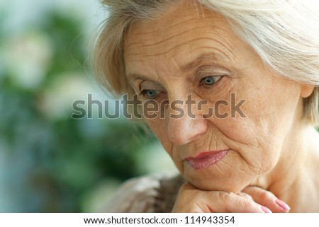 portrait of a beautiful older woman on a summer background - stock photo