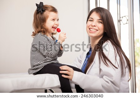 Portrait of a beautiful pediatrician with a happy little girl as her patient enjoying a lollipop and smiling - stock photo