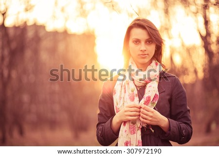Portrait of a beautiful pensive girl in a park at sunset, warm colors - stock photo
