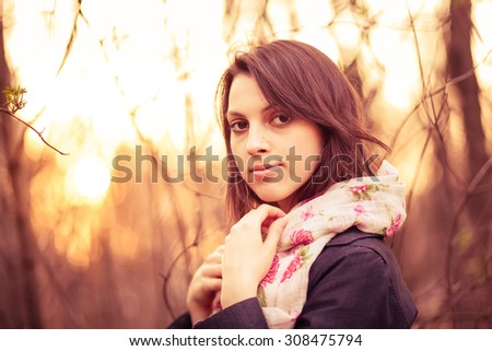 Portrait of a beautiful pensive girl in a park at sunset, warm colors, closeup - stock photo