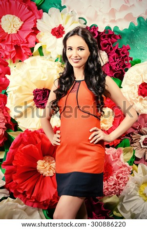 Portrait of a beautiful pregnant woman posing over big bright flowers. Clothes for pregnant women. Beauty, fashion. - stock photo