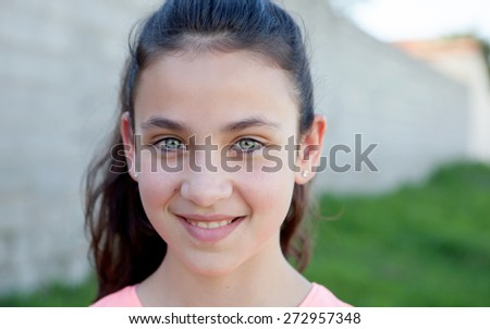 Portrait of a beautiful preteen girl with blue eyes outside - stock photo