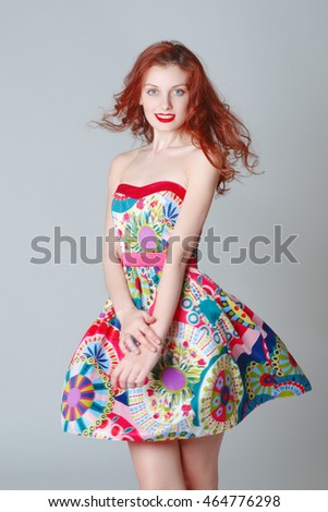 Portrait of a beautiful red-haired girl in dress in Studio on gray background