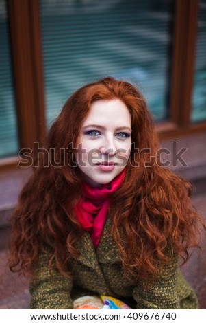 Portrait of a beautiful redhead woman in pink scarf and green coat, closeup, serious - stock photo